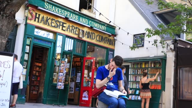 "person reading a book in front of the bookstore specializing in english literature ""shakespeare and company"" on july 19, 2020 in paris, france. this... - learning stock videos & royalty-free footage"