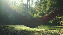 A person reading book in hammock at garden