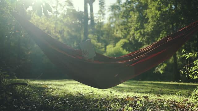 en person som läser bok i hängmatta på trädgård - hängmatta sol bildbanksvideor och videomaterial från bakom kulisserna
