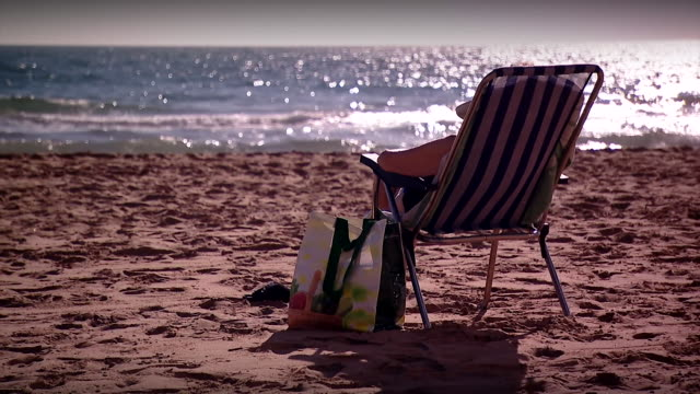 a person relaxing on a deck chair - outdoor chair stock videos & royalty-free footage