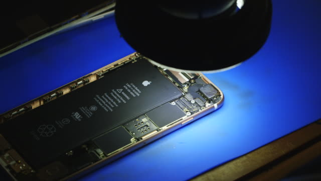 Person repairs iphone, electronics