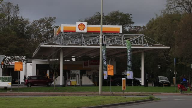 person rides a bike near an oil giant shell gas station on october 18, 2020 in the hague, the netherlands. the british-dutch group wants to cut up to... - architecture stock videos & royalty-free footage