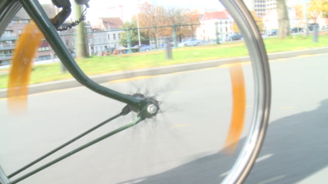 cu ts person riding bicycle on street, gent, belgium - wheel stock videos & royalty-free footage