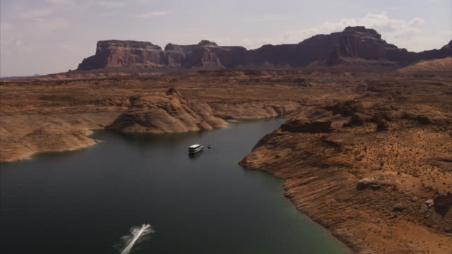 person riding jet boat in desert lake passing boat / lake powell, arizona, united states - lake powell stock videos and b-roll footage