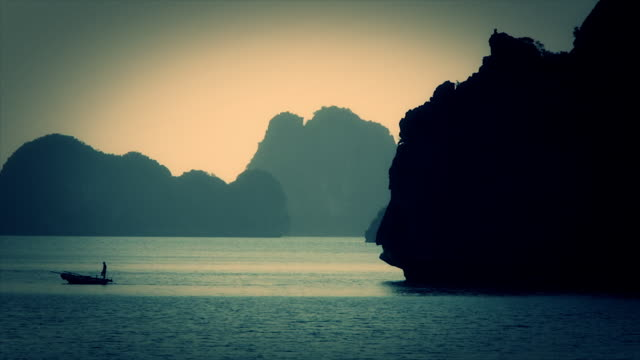 ws person rowing fishing boat in ha long bay / vietnam - halong bay stock videos and b-roll footage