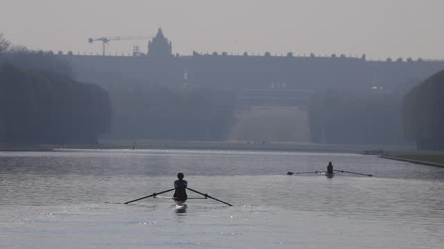 person rows on the grand canal in the park of the chateau de versailles at sunrise amid a covid-19 outbreak on april 21, 2021 in versailles, france.... - atmosphere filter stock videos & royalty-free footage