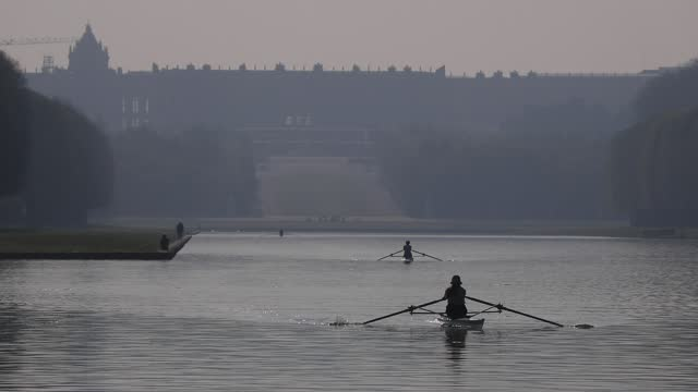 person rows on the grand canal in the park of the chateau de versailles at sunrise amid a covid-19 outbreak on april 21, 2021 in versailles, france.... - atmosfär evenemang bildbanksvideor och videomaterial från bakom kulisserna