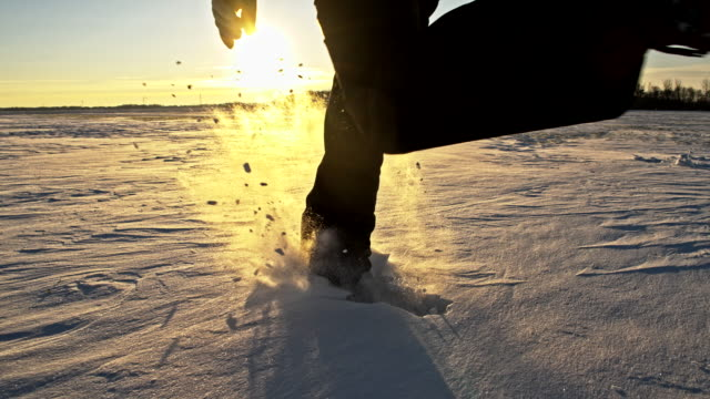 slo mo person running in snow at sunset - footprint stock videos and b-roll footage