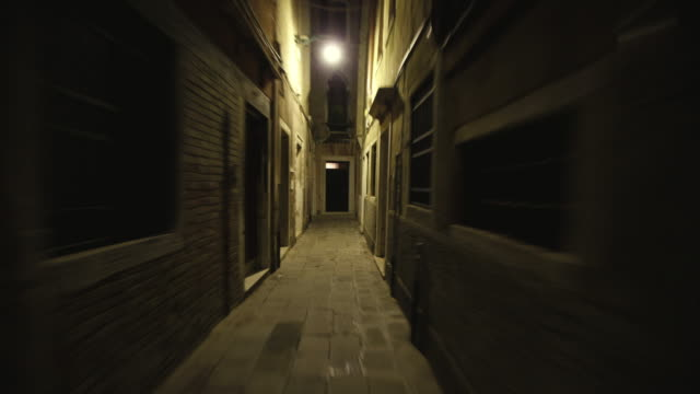 T/L POV Person running through narrow alleys in San Marco district at night, Venice, Veneto, Italy
