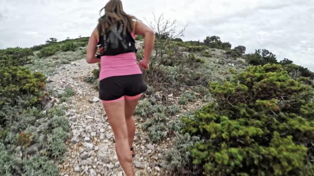 vidéos et rushes de pov personne fonctionnant vers le haut de la montagne sur un sentier rocailleux derrière une femme - qui monte