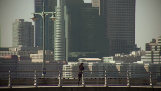 a person runs down a pier in the hudson river park the jersey city skyline is behind - 女性ランナー点の映像素材/bロール