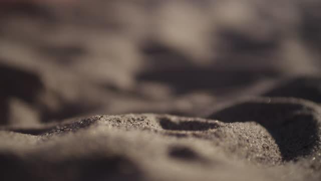 Person runs fingers through sand, close up
