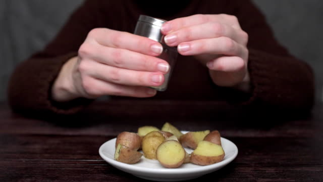 person salting fried potatoes - fried potato stock videos and b-roll footage