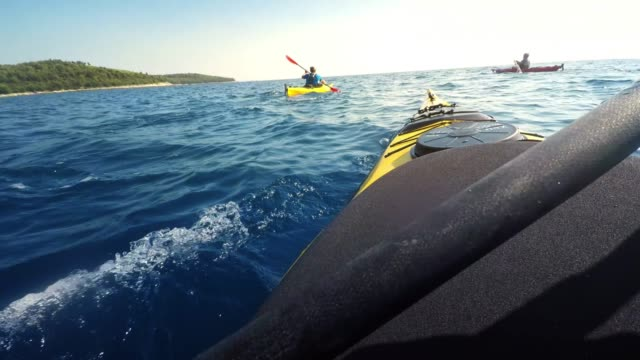 pov person sea kayaking with friends in sunshine and stopping to relax - esplorazione video stock e b–roll