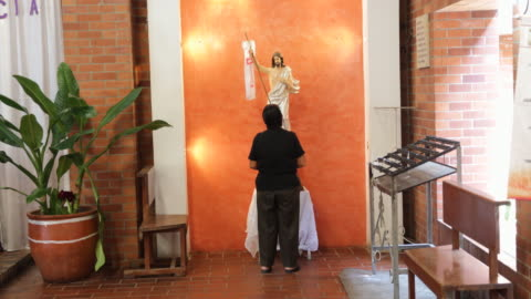 vídeos y material grabado en eventos de stock de person, shot from the back, is standing and praying before a religious sculpture inside a church. - cristianismo