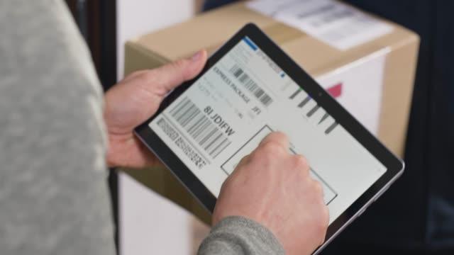 パッケージを受け取るためにデジタルポッドに署名する人 - 署名する点の映像素材/bロール