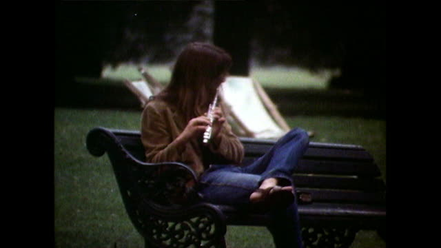person sits on park bench playing the flute; 1971 - hippy stock videos & royalty-free footage