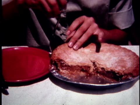 CU Person slicing piece of apple pie and serving it on plate / USA