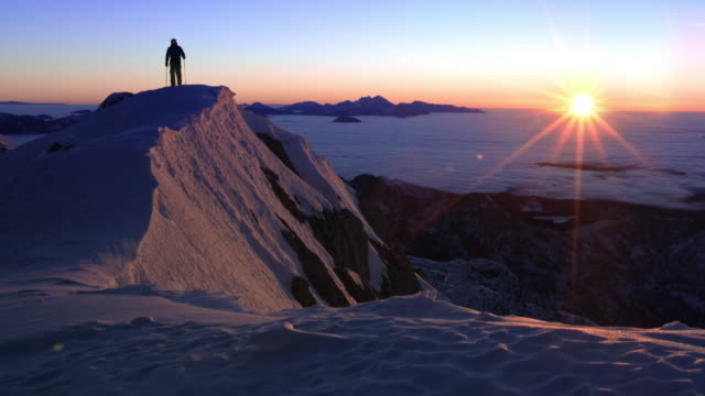 DS Person snowshoeing across a mountain ridge at sunset