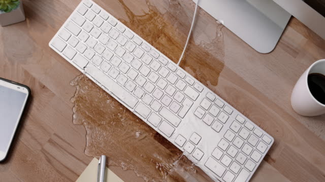 vídeos de stock e filmes b-roll de slo mo ld person spilling a glass of water on a white keyboard in the office - teclado de computador