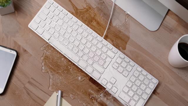 vidéos et rushes de slo mo ld personne renverser un verre d'eau sur un clavier blanc au bureau - tasse à café