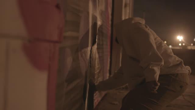 person sprays graffiti on building at night, medium shot - 公共物破壊点の映像素材/bロール