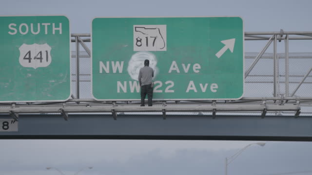 person sprays graffiti on highway sign during day, wide shot - graffiti stock videos & royalty-free footage