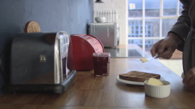 Person spreading butter and jam on toast