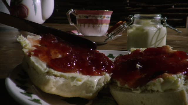 person spreads jam onto scones on table, uk - tea cup stock videos & royalty-free footage