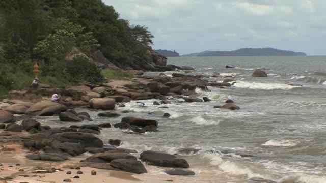 ws person squatting on rocks watching sea, sihanouksville, cambodia - cambodia stock videos & royalty-free footage