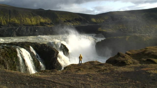 ws person standing on edge of dynkur waterfall, looking at view / iceland - island stock-videos und b-roll-filmmaterial