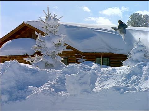 vídeos de stock e filmes b-roll de person standing on roof of cabin shoveling off snow - pá para neve
