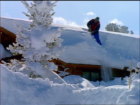 vídeos de stock e filmes b-roll de person standing on roof of cabin shoveling off snow vigorously - pá para neve