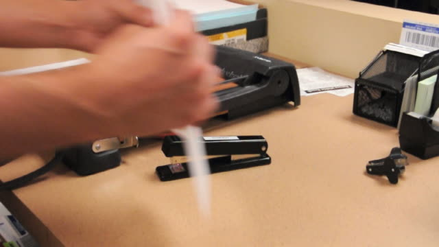 CU Person stapling stack of papers, Los Angeles, California, USA