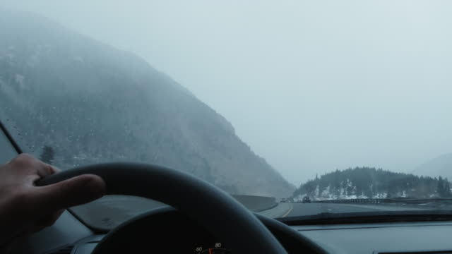 eine person steuert das lenkrad eines fahrzeugs während der fahrt auf der interstate 70 in den rocky mountains von colorado an einem verschneiten tag im winter - lenkrad stock-videos und b-roll-filmmaterial