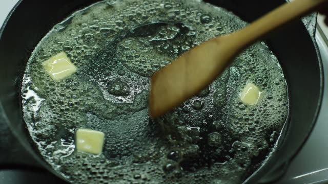 a person stirs pats of butter with a wooden spatula as they melt in a black cast iron skillet on a stove - appliance stock videos & royalty-free footage