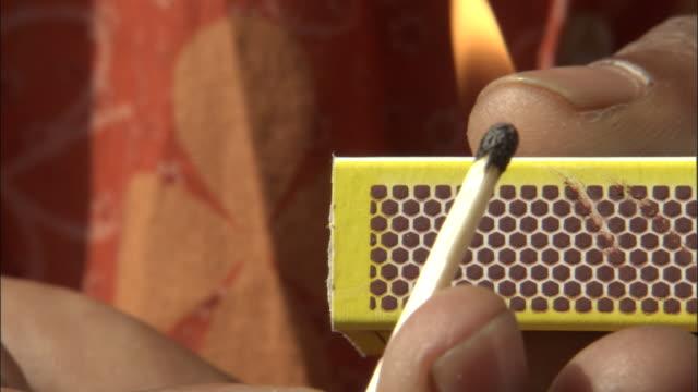 vídeos de stock e filmes b-roll de a person strikes a match on the side of a matchbox. available in hd. - caixa de fósforos