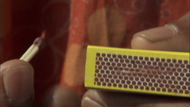 stockvideo's en b-roll-footage met a person strikes a match on the side of a matchbox. available in hd. - lucifer