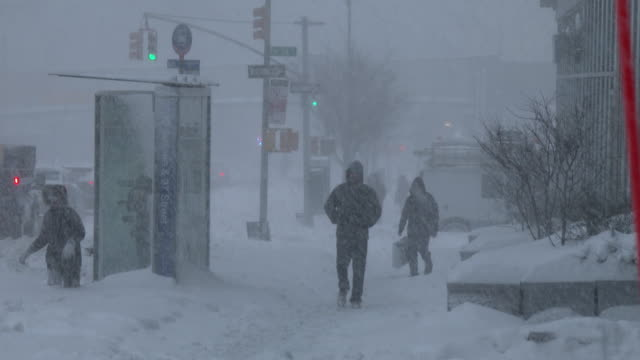 a person stumbles and falls in deep snow as other pedestrians struggle in near whiteout conditions along 10th avenue on the west side of manhattan... - gale stock videos and b-roll footage