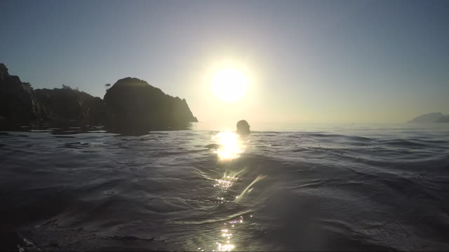 POV of person swimming through tranquil sea, towards others