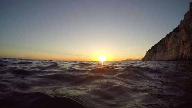 POV Person swimming up to the surface and looking into the setting sun