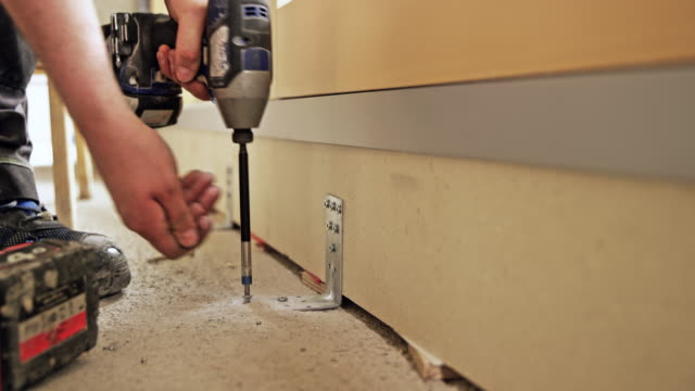 person tightening screws into the floor with a machine - work tool stock videos & royalty-free footage