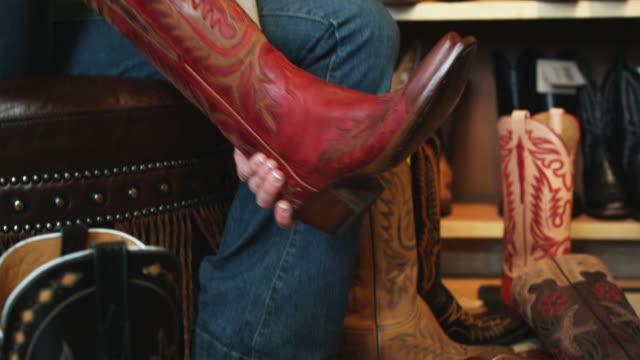 vídeos de stock, filmes e b-roll de person trying on cowboy boots - só uma mulher de idade mediana