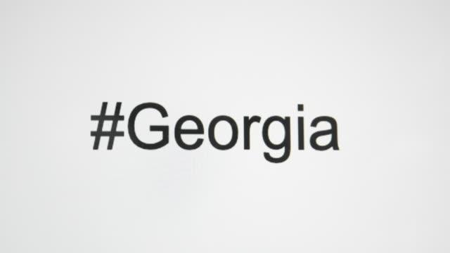 """vídeos y material grabado en eventos de stock de un tipo de persona """"#georgia"""" en la pantalla de su ordenador y luego sigue con la abreviatura de estado - georgia"""