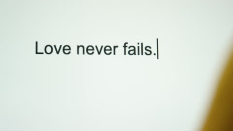 """a person types """"love never fails"""" on their computer screen - christianity stock videos & royalty-free footage"""