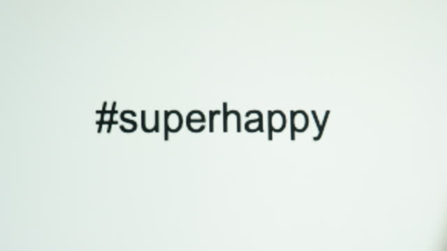 "a person types ""#superhappy"" on their computer screen - estatico video stock e b–roll"