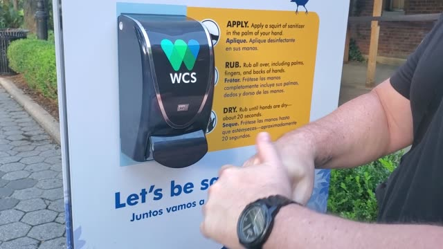 person uses a hand sanitizing station at the entrance of central park zoo as the city continues phase 4 of re-opening following restrictions imposed... - セントラルパーク動物園点の映像素材/bロール