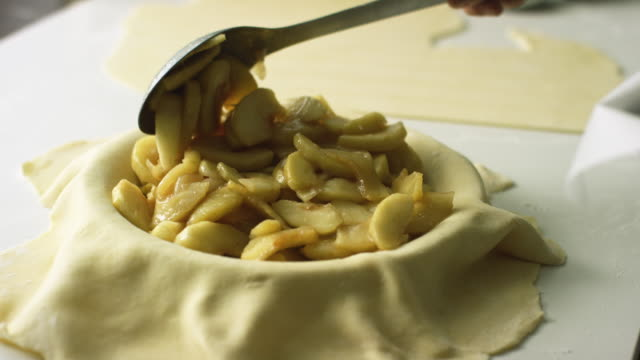 a person uses a large metal spoon to scoop cooked and peeled apple slices (filling) from a covered baking sheet to a pastry-covered pie tin while making an apple pie - preparation stock videos & royalty-free footage