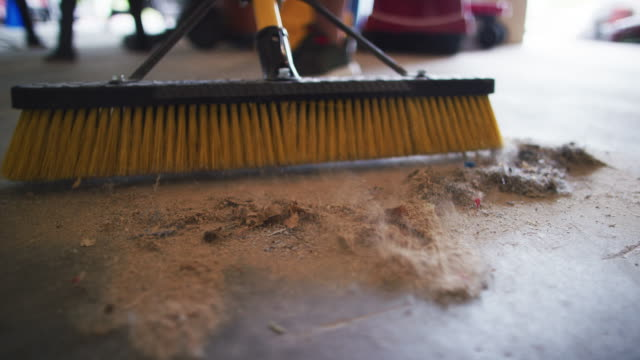 a person uses a long push broom to sweep sawdust shavings into a pile on the floor of a garage - caretaker stock videos & royalty-free footage