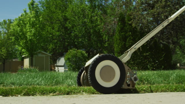 A Person Uses a Manual Push Lawn Mower to Cut the Grass in a Residential Neighborhood on a Sunny Day